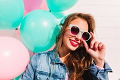 Adorable brunette young woman looking through stylish sunglasses and posing with smile next to colorful balloons. Close