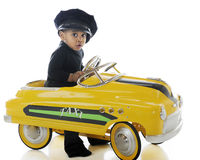 Adorable Cabbie. An adorable toddler driving a yellow pedal car while wearing a cab drive's hat.  On a white background Royalty Free Stock Images