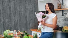 Adorable casual young girl sniffing pink gentle flower bouquet in kitchen at home