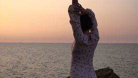 Adorable caucasian brunette girl in light dress dancing at the cliff above the sea at sunrise time. 4k uhd stock video footage