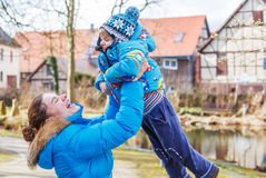 Adorable caucasian little boy and mother hugging on bridge, outd Stock Image