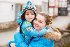Adorable caucasian little boy and mother hugging on bridge, outd. Cute caucasian little boy and his mother hugging on bridge, outdoors on cold day Stock Photography