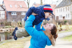 Adorable caucasian little boy and mother hugging on bridge, outd Stock Images