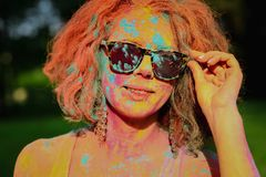 Adorable caucasian model wearing glasses covered by dry Holi paint. Adorable caucasian woman wearing glasses covered by dry Holi paint stock photos