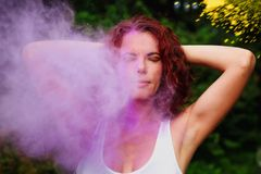 Adorable caucasian model with curly hair posing in a cloud of pu. Adorable caucasian woman with curly hair posing in a cloud of purple and yellow Holi paint stock images