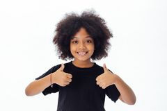 Adorable and cheerful African American kid with afro hairstyle giving thumbs up stock photo