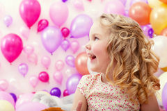 Adorable cheerful girl on balloons background Royalty Free Stock Photos