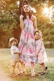 Adorable, cheerful kids holding their mother`s legs royalty free stock image