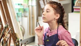 Cute little girl showing thumbs up while painting a picture at the art class. Adorable cheerful little girl examining her painting smiling to the camera showing stock image