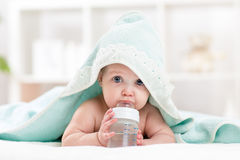 Adorable child baby drinking water from bottle. Little girl  wrapped bathing towel lying on bed Royalty Free Stock Photography