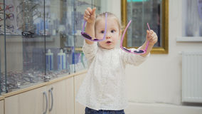 Adorable child blonde girl in ophthalmology clinic plays in hall near glasses store Royalty Free Stock Photo