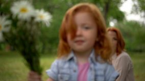Adorable child with bouquet. Beautiful Little Girl With Mom In Park. Made Nice Bouquet For Mom. Mom And Little Daughter Concept stock footage