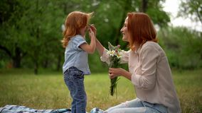 Adorable child with bouquet. Little Daughter Presented Mom With Bouquet While Spending Time Together In Park stock video footage