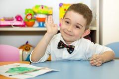 Adorable child boy draws a brush and paints in nursery room. Kid in kindergarten in Montessori preschool class. stock photo