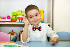 Adorable child boy draws a brush and paints in nursery room. Kid in kindergarten in Montessori preschool class. stock photos