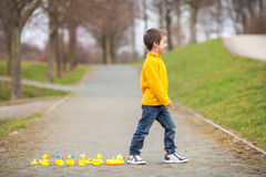Adorable child, boy, playing in park with rubber ducks, having f Stock Photography