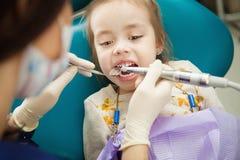 Adorable child calmly goes through procedure of teeth polishing Stock Photography