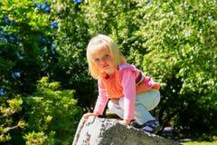 Adorable child climbing stone wall. Christchurch Botanic Garden. Stock Photos