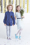 Adorable child couple. Girl holding bouquet of flowers stock image
