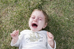 Adorable child crying and lying in the garden Stock Image