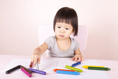 Adorable child drawing with colorful crayons. Adorable child drawing with colorful crayons and smiling, with the copy space royalty free stock images