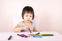 Adorable child drawing with colorful crayons. Adorable child drawing with colorful crayons and smiling, with the copy space royalty free stock photography