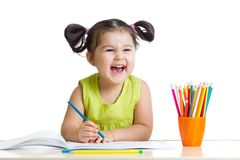 Adorable child drawing with colorful crayons and. Smiling, isolated on white stock photos