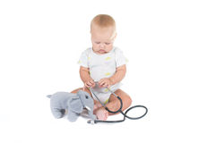 Adorable child dressed as doctor playing with toy Royalty Free Stock Image
