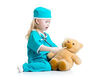 Adorable child dressed as doctor playing with toy Stock Image