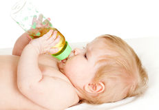Adorable child drinking from bottle. 6 months old girl Stock Photo