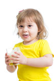 Adorable child drinking milk with milk mustache holding glass of milk. Adorable child girl drinking milk with milky mustache holding glass of milk Stock Photo