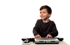 Adorable child with electric piano and laptop Royalty Free Stock Image