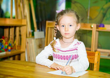 Adorable child girl drawing with colorful pencils in nursery room. Kid in kindergarten in Montessori preschool class. Stock Photography