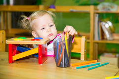 Adorable child girl drawing with colorful pencils in nursery room. Kid in kindergarten in Montessori preschool class. Royalty Free Stock Image