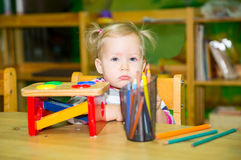Adorable child girl drawing with colorful pencils in nursery room. Kid in kindergarten in Montessori preschool class. Royalty Free Stock Photography