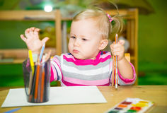 Adorable child girl drawing with colorful pencils in nursery room. Kid in kindergarten in Montessori preschool class. stock images