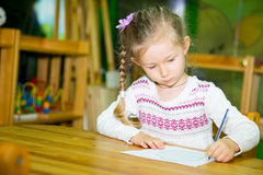 Adorable child girl drawing with colorful pencils in nursery room. Kid in kindergarten in Montessori preschool class. Adorable child girl drawing with colorful royalty free stock images