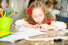 Adorable child girl drawing with colorful pencils in nursery room. Kid in kindergarten in Montessori preschool class. Adorable child girl drawing with colorful stock photos