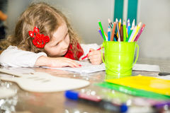 Adorable child girl drawing with colorful pencils in nursery room. Kid in kindergarten in Montessori preschool class. Adorable child girl drawing with colorful royalty free stock photo