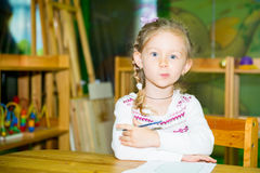 Adorable child girl drawing with colorful pencils in nursery room. Kid in kindergarten in Montessori preschool class. royalty free stock photo