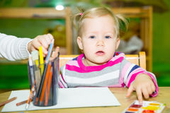 Adorable child girl drawing with colorful pencils in nursery room. Kid in kindergarten in Montessori preschool class. stock image