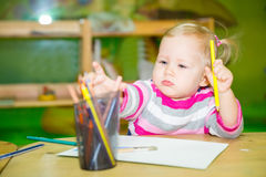 Adorable child girl drawing with colorful pencils in nursery room. Kid in kindergarten in Montessori preschool class. Adorable child girl drawing with colorful stock image
