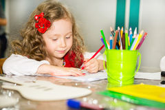 Adorable child girl drawing with colorful pencils in nursery room. Kid in kindergarten in Montessori preschool class. Adorable child girl drawing with colorful stock photography