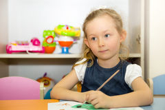 Adorable child girl draws a brush and paints in nursery room. Kid in kindergarten in Montessori preschool class. Royalty Free Stock Image