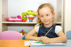 Adorable child girl draws a brush and paints in nursery room. Kid in kindergarten in Montessori preschool class. Royalty Free Stock Photo