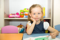 Adorable child girl draws a brush and paints in nursery room. Kid in kindergarten in Montessori preschool class. Adorable child girl draws a brush and paints in stock image