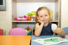 Adorable child girl draws a brush and paints in nursery room. Kid in kindergarten in Montessori preschool class. stock image