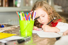 Adorable child girl draws a brush and paints in nursery room. Kid in kindergarten in Montessori preschool class. Adorable child girl draws a brush and paints in royalty free stock photography