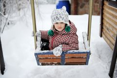 Adorable child girl enjoys seesaw in winter Stock Photo