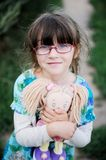 Adorable child girl in glasses hugs baby doll Royalty Free Stock Images